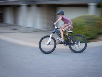 Ein Junge mit Helm saust auf einem Mountainbike um eine Ecke.