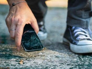 Hand hebt kaputtes Smartphone auf