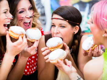 Eine Gruppe Frauen feiert Karneval und isst Berliner
