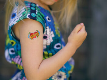 """Ein blondes Kind hat ein """"Mom""""-Klebetattoo mit Herz auf dem Arm."""