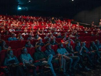 Viele Menschen in einem Kinosaal in roten Sesseln.