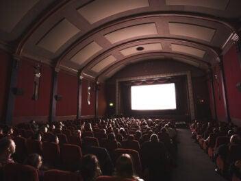 Menschen schauen einen Film aus den 1940er Jahren in einem alten Kinosaal.