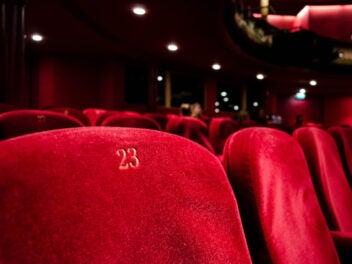 Rote Kinosessel im Fokus, mit goldener Zahl bestickt und Lichtern im Hintergrund