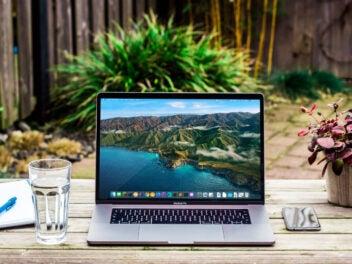 Ein Laptop auf einem Tisch, neben einem iPhone und einer Pflanze