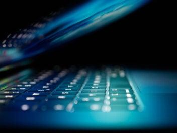 Ein halb zugeklappter Laptop mit aktivem Bildschirm, der die Tastatur anleuchtet.