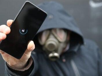 Mann mit Gasmaske hält LG G7 ThinQ mit Bootloop in die Kamera