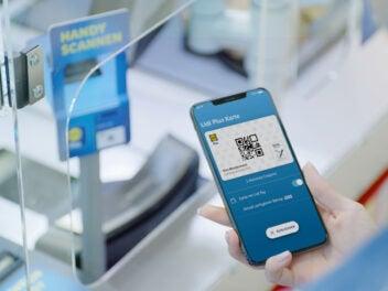Lidl Pay auf einem Smartphone, im Hintergrund eine Kasse
