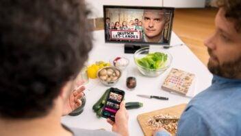 Zwei Darsteller zeigen Magenta TV auf dem Smartphone und Fernseher und sind dabei am Kochen.