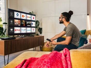 Ein Mann sitzt auf einer Couch im Wohnzimmer. Auf dem Fernseher ist Magenta TV zu sehen