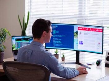 Mann vor großem Monitor am Schreibtisch