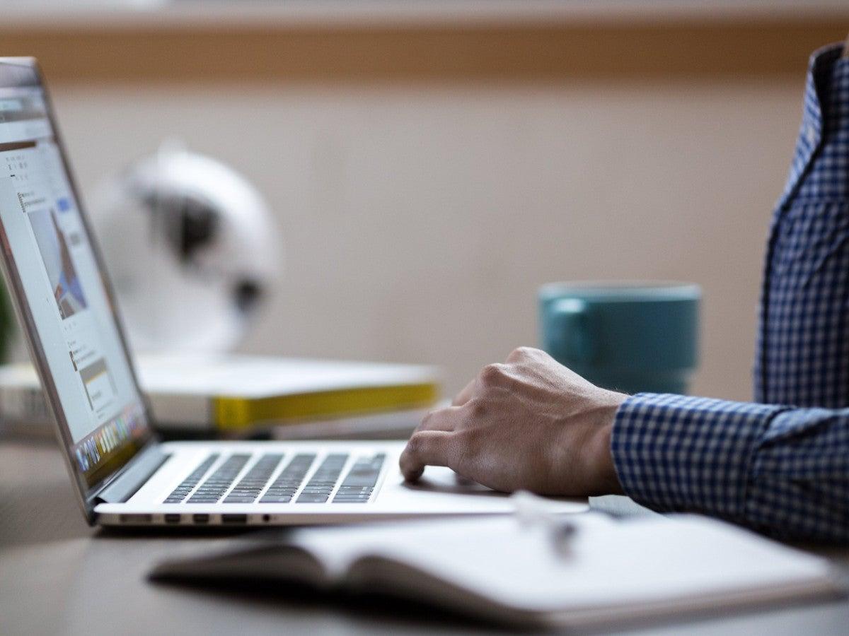 Mann an einem Laptop mit Kaffeetasse