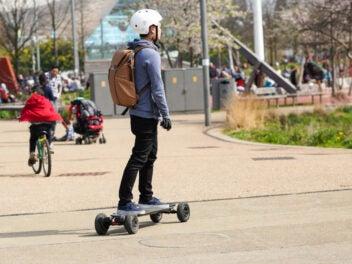 Ein Mann mit Helm fährt mit einem E-Skateboard über einen Platz.