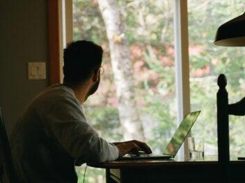Ein Mann sitzt an einem Tisch vor seinem Laptop