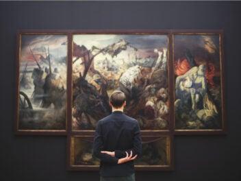 Ein Mann steht vor einem großen Gemälde mit dem Rücken zur Kamera.