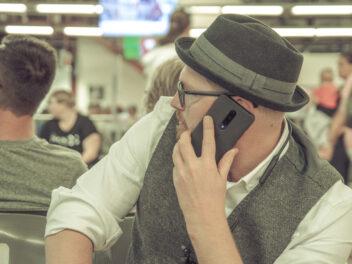 Mann telefoniert mit Handy im Flughafen