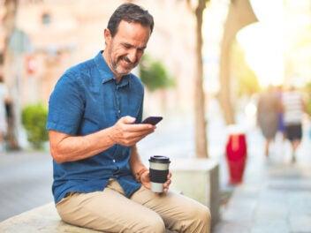 Mann mit Kaffee und Smartphone