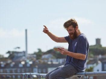 Mann mit Smatphone beim Jubel