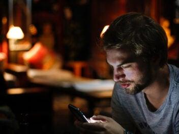 Mann nutzt ein Smartphone in einem abgedunkelten Raum.