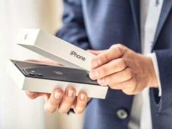 Ein Mann öffnet einen Karton des iPhone 12