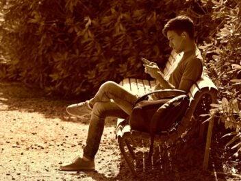 Ein Man sitzt auf einer Parkbank und nutzt sein Handy