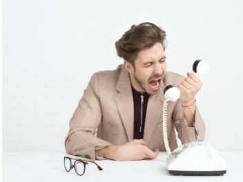 Junger Mann schreit in einen Festnetz-Telefonhörer