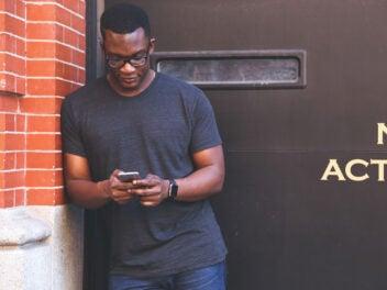 Mann lehnt lässig an Mauer und schaut auf sein Smartphone