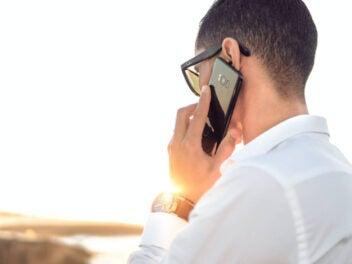 Mann telefoniert mit einem Smartphone im Sonnenlicht