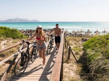 Mann und Frau mit Fahrrad am Strand