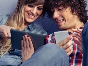 Mann und Frau mit einem Smartphone und einem Tablet