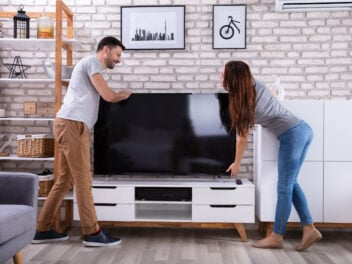 Frau und Mann stellen einen Fernseher auf