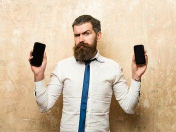 Mann hält zwei Handys in seinen Händen