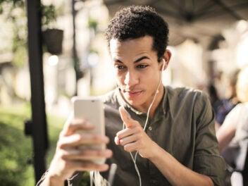 Ein junger Mann mit schwarzen Locken redet auf sein Smartphone ein und hat Kopfhörer in den Ohren