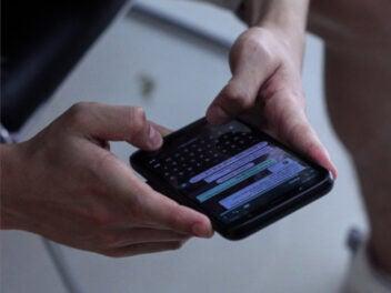 Ein Mann sitzt auf einem Stuhl, seine Hände halten ein Smartphone das im Fokus des Bildes steht, im Hintergrund sieht man seine Beine.