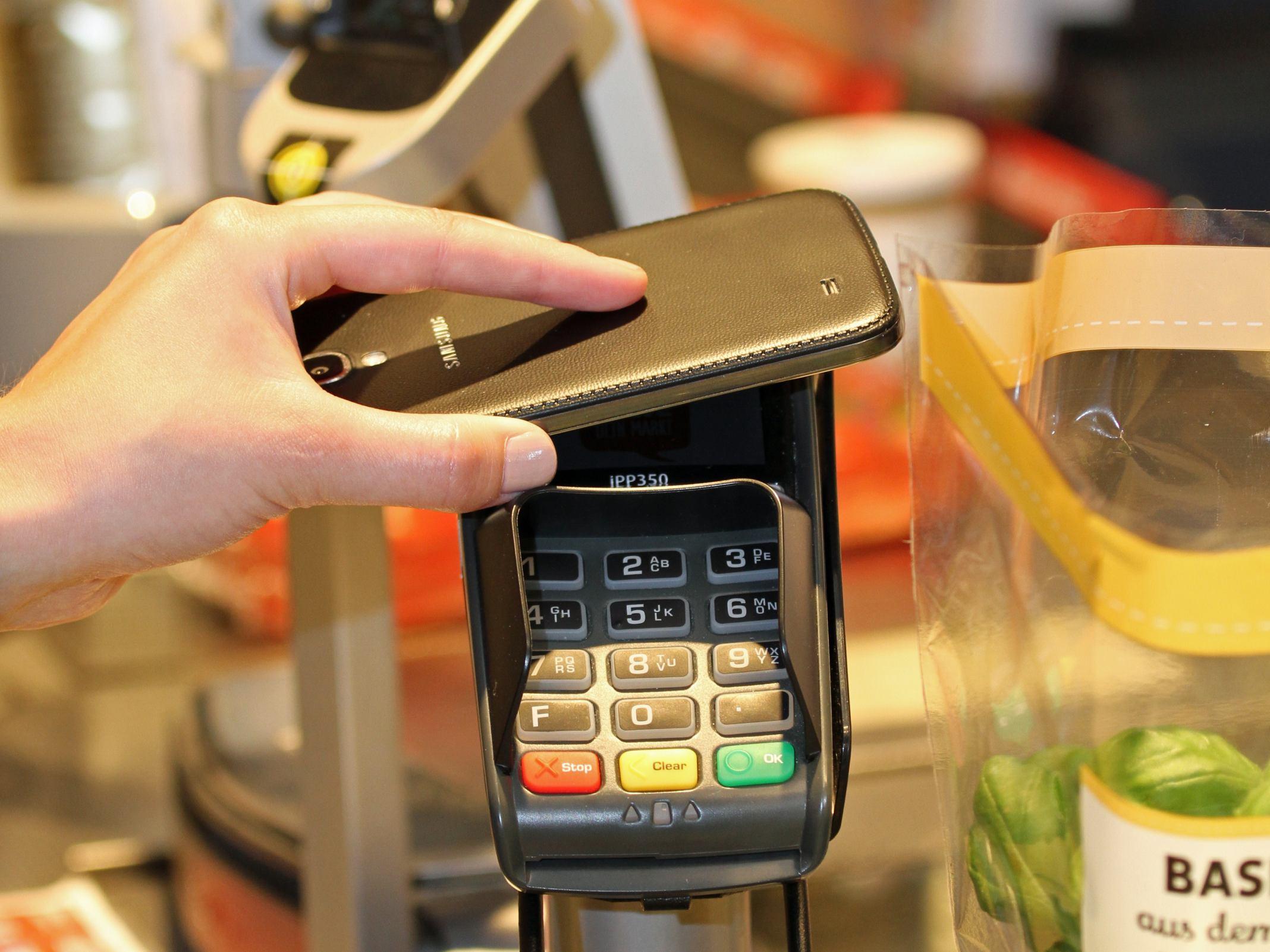Ein Handy wird an ein Kartenterminal im Handel gehalten