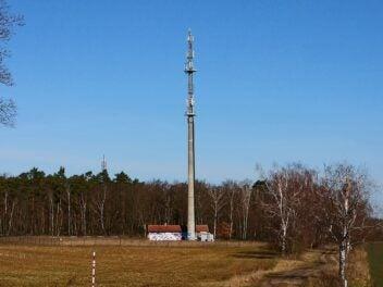 Ein Sendemast mit Mobilfunkantennen auf einer Wiese vor einem Wald