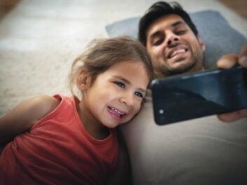Mann und Kind nutzen ein Smartphone