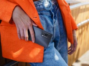 Das Motorola Edge 20 Smartphone in der Hand einer Frau, die es vor ihre Jeans hält