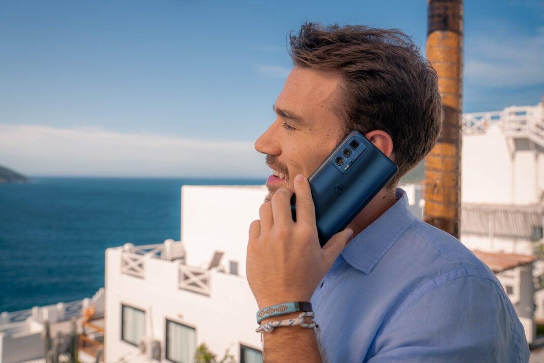Das Motorola Edge 20 Pro Smartphone in der Hand eines Mannes, der telefonierend vor dem Meer steht