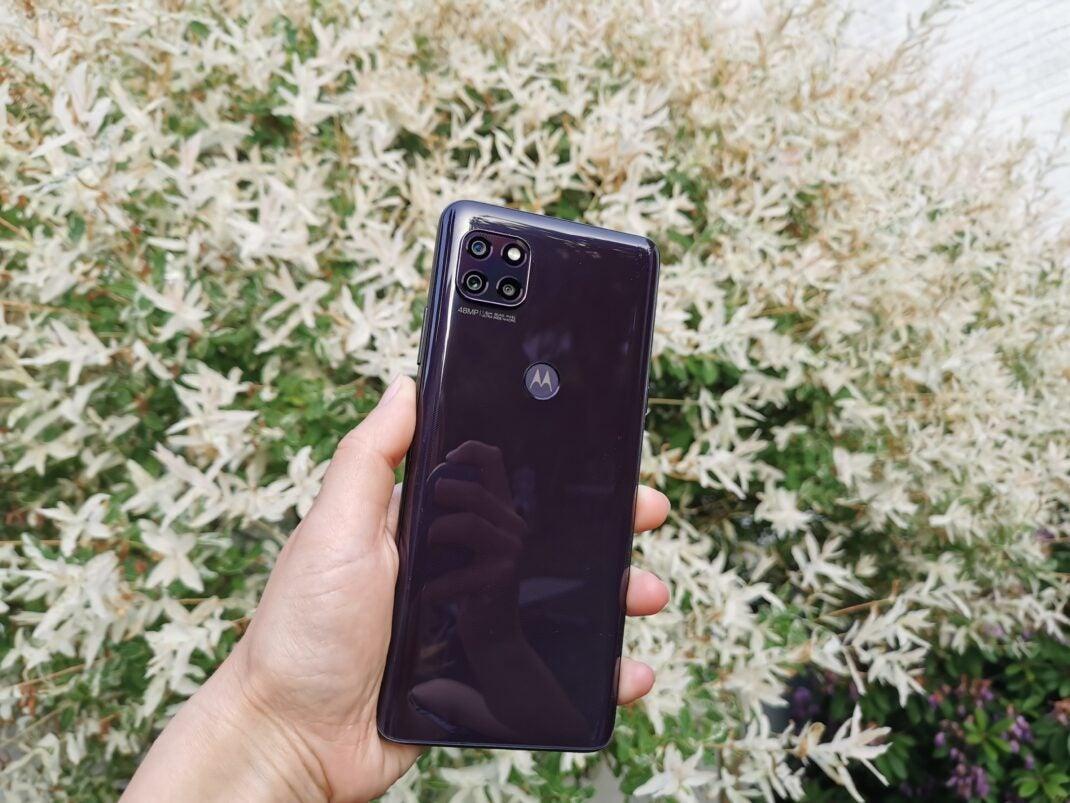 Die schwarze Rückseite des Motorola Moto G 5G vor einem weißen Busch