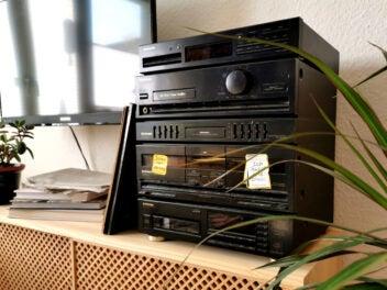 Alte Stereoanlage auf einem Holz-Sideboard neben einer Pflanze und einem TV
