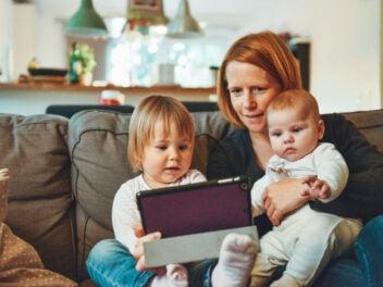 Frau mit zwei Kindern auf dem Sofa