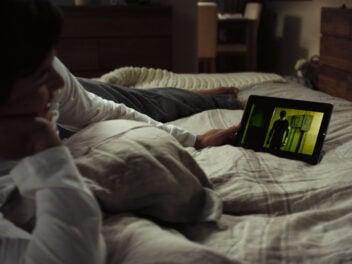 Mann liegt im Bett und schaut Netflix auf einem Tablet