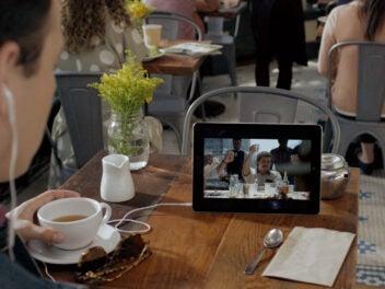Mann streamt eine Serie auf einem Tablet-PC und trinkt dabei Tee