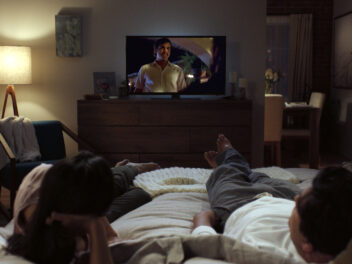 Ein Paar liegt auf dem Bett und schaut eine Serie auf dem Fernseher