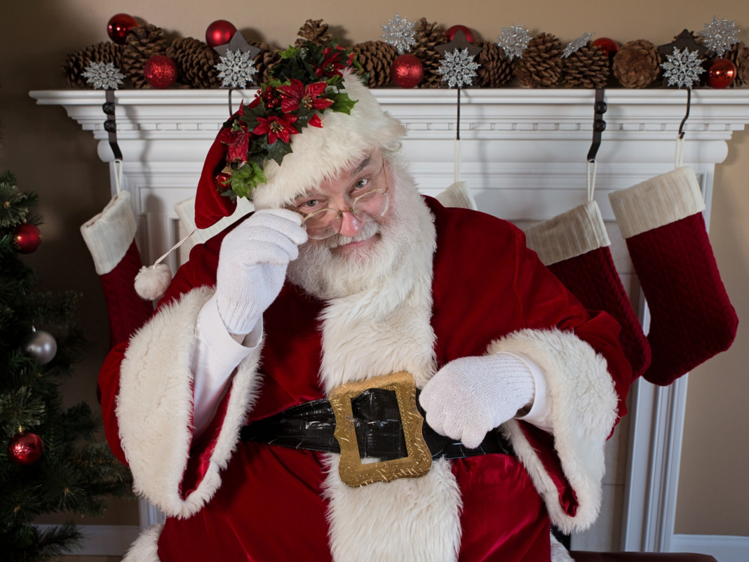 Weihnachtsmann oder Nikolaus sitzt vor dem Kamin