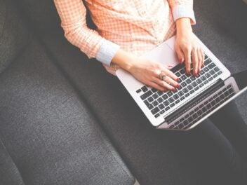 Mit dem Notebook auf der Couch: Hände bedienen einen Rechner