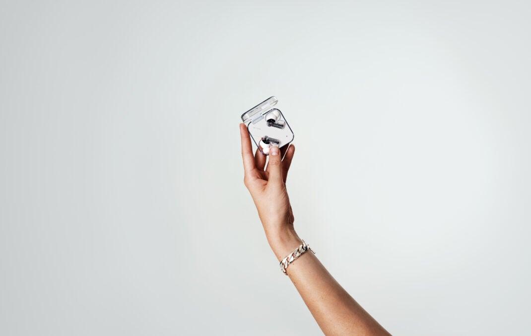 Die Kopfhörer Nothing Ear 1 in ihrem Case in einer Hand.