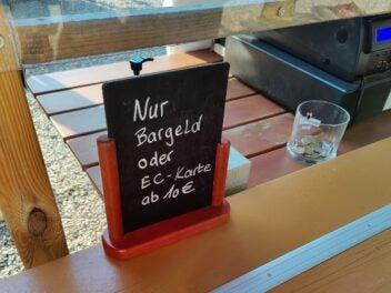 """Ein Schild an einer Kasse: """"Nur Bargeld oder EC-Karte ab 10 Euro"""""""