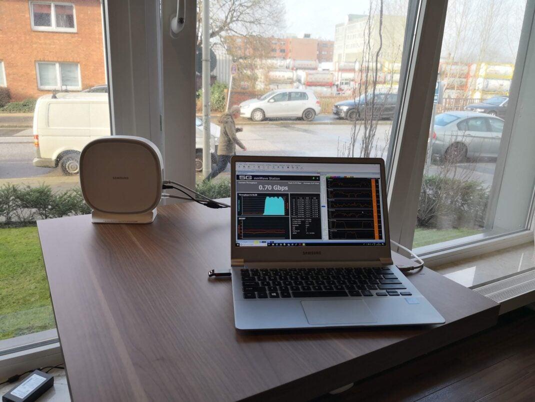Eine Antenne und ein Laptop mit Speedtest stehen auf einem Tisch am Fenster