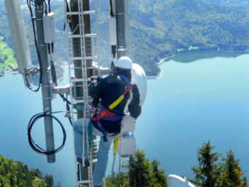 Mann installiert Antennen auf Mast